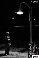 Standing lights (Alesfra) Tags: street camera light shadow portrait blackandwhite bw espaa white man black blancoynegro blanco luz silhouette grancanaria night composition standing port puerto island glasses noche photo spain farola streetlight foto photographer darkness retrato negro sombra canarias bn panasonic gafas silueta canaryislands isla fotgrafo hombre omd oscuridad cmara em1 composicin agaete laspalmasdegrancanaria puertodelasnieves mirrorless alesfra albertojespieirafrancs alesfraphotography alesfrafotografia wwwalesfracom olympusem1 olympusomdem1 panasonic35100f28 panasoniclumixgxvario35100mmf28