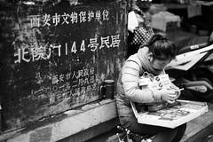 Head's down (ah.b|ack) Tags: china street bw zeiss t 50mm head sony down souvenir xian sit stare seller handphone wideopen f15 sonnar zm a7ii zeisscsonnart1550mmzm a7mk2