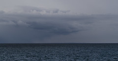 Cloud Over an Island (brucetopher) Tags: ocean light sea cloud snow storm water rain weather clouds squall bay coast stormy coastal shore ripples seashore coasline squalls