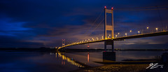 I Feel It Coming In Waves (Tim van Zundert) Tags: bridge blue light england sky panorama cloud reflection water wales night river lights evening coast long exposure sony south voigtlander gloucestershire rye severn shore pollution hour chepstow 219 21mm ultron beachley a7r