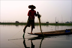 Leg-rowing (*Kicki*) Tags: houses sky lake man reflection net water hat silhouette person 50mm boat fishing fisherman burma horizon canoe oar myanmar inlelake inle balance shanstate inlay fishingnet hardworking legrowing inlaylake