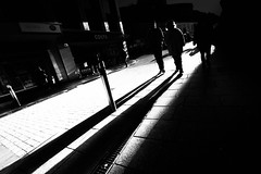 And still they cast their shadows... (pootlepod) Tags: life street blue windows winter girls light sky people blackandwhite woman sun sunlight white man black reflection male green monochrome yellow sex female contrast shopping dark photography shadows view post pavement candid sidewalk study shade blocks cracks length ong canon60d stphotographia