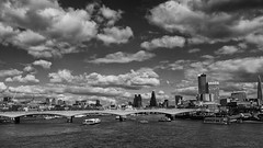 a city keeps its head in the clouds (lunaryuna) Tags: uk bridge sky bw panorama london water monochrome beauty sunshine thames skyline architecture clouds buildings river season boats pier blackwhite spring britain lunaryuna riverthames cloudscape waterloobridge southbankcenter doubledeckerbusses urbanconstructs seasonalwonders cranesgalore theemergenceofred