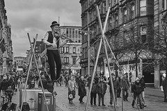 The man on a rope (dscott14) Tags: street mono blackwhite audience glasgow buchananstreet rope violin bowlerhat tightrope streetentertainer onlookers metalsupports