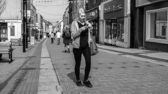 She loves her Mobile (Howie Mudge LRPS) Tags: road street uk travel windows portrait people urban blackandwhite bw woman men travelling monochrome wales architecture buildings bench mono blackwhite women doors chairs pavement candid cymru bangor streetphotography streetlife panasonic shops casual posts everydaylife gwynedd towncenter urbanphotography m43 mft micro43 microfourthirds mirrorlesscamera compactsystemcamera lumixgvario1442f3556ii micro43mountlenses panasonicdmcgx8 169perspective