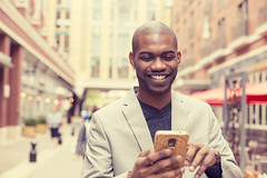 happy smiling urban professional man using smart phone (Yardstick Marketing) Tags: street city summer portrait people urban man black male men smile face smart mobile outside happy person student holding media technology message phone outdoor expression african text unitedstatesofamerica cellphone cell handsome lifestyle cellular content social professional using business suit smartphone latin casual messenger network concept talking ethnic app sms texting businessmen