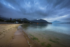 Stormy Shore on Itsukushima (ErikFromCanada) Tags: blue mountain storm mountains reflection beautiful japan fog clouds dark landscape island japanese reflecting coast haze sand gate waves cloudy dramatic wave wideangle stormy hiroshima shore swell torri itsukushima a7r