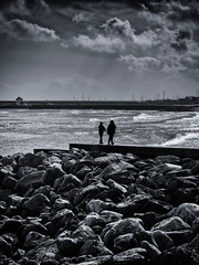 walking on water (martin_rees) Tags: sun beach monochrome silhouette clouds contrast seaside rocks waves harbour dorset cobb nik backlit walkers lymeregis silverefex