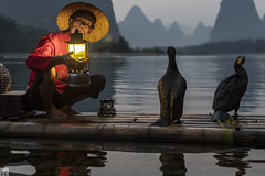 Light A Fire on Li River (lycheng99) Tags: china light sunset red portrait people mountains nature lamp face birds reflections river cormorants landscape fire lights liriver fishing fisherman dusk guilin bamboo gaslamp cormorant raft reflectingpool karst guangxi bambooraft chinatravel líjiāng flickrdiamond karstformation