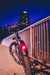Blue hour stop (thethomsn) Tags: bridge light red bike bicycle wheel skyscraper fence germany dof bokeh sigma sidewalk stop bluehour augsburg blauestunde 30mm hotelturm thethomsn