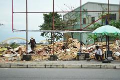 Amid the rubble (Roving I) Tags: progress vietnam seats bags chewinggum umbrellas development rubble danang scavenging streetvendors doublemint wrigleys frameworks dragonbridge conicalhats