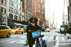 Citibiker in Midtown. (stillsguy) Tags: nyc blue film 50mm nc spring ride skyscrapers traffic bokeh f14 young streetphotography olympus midtown 400 pedestrians tall expired cabs rider portra zuiko preparing om2n citibike bokehlicious