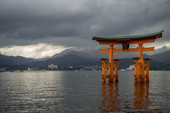 Floating Torii Under a Silvery Light (Aymeric Gouin) Tags: voyage travel light sea sky orange mer seascape water japan clouds dark landscape seaside gate eau lumire olympus miyajima ciel sombre silvery nuage nuages paysage torii japon omd itsukushima floatingtorii littoral em10 aymgo aymericgouin