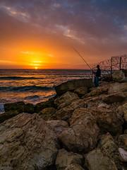 Catching some sun. (ozzios) Tags: sunset sea nature clouds fence harbor israel telaviv fisherman rocks il telavivyafo telavivdistrict