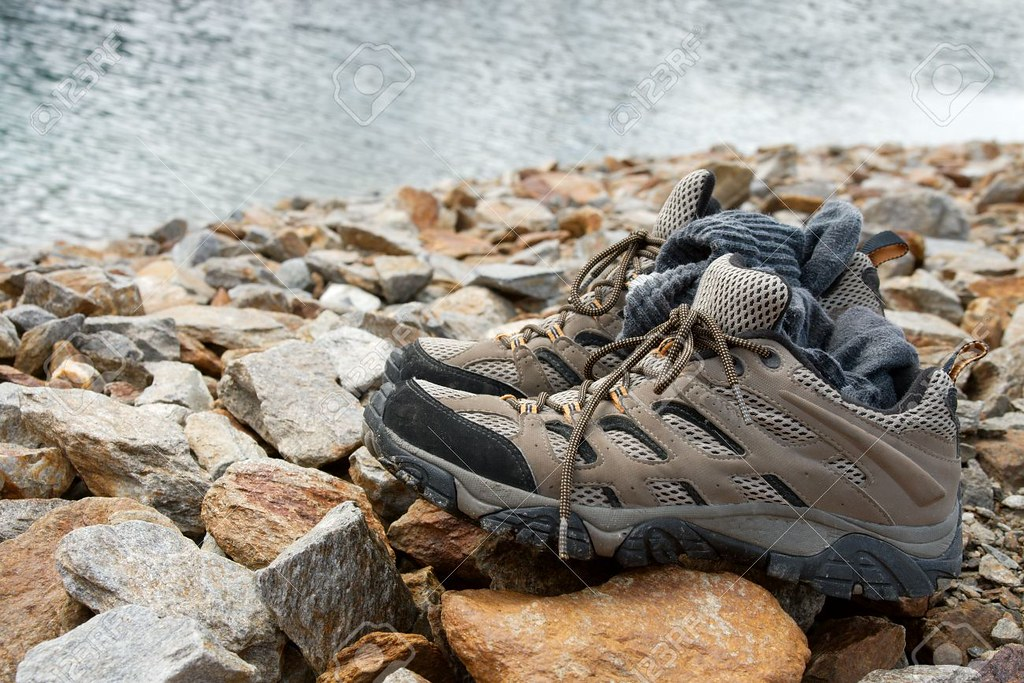 6620318-Hiking-shoes-on-the-rocks-next-to-a-mountain-lake-Stock-Photo