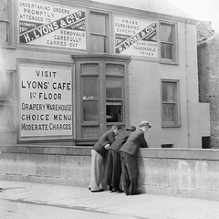 Three men at bridge - ads on wall for Lyons cafe and goods.