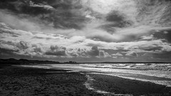 a sky as vast and tumultous as the sea below (lunaryuna) Tags: ocean light sea sky bw panorama sunlight storm beach monochrome beauty wales season landscape island coast blackwhite spring waves atlantic textures shore lunaryuna cloudscape stormclouds anglesey northwales seascaoe rhosneigrbeach seasonalwonders