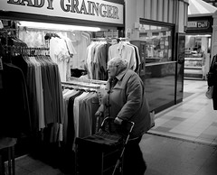 An Old Lady in the Grainger Market - Newcastle (Richard James Palmer) Tags: street new uk portrait england urban blackandwhite white abstract black art 120 mamiya film monochrome newcastle photography trapped shoot gloomy iso400 fineart north streetphotography documentary overcast rangefinder gritty ishootfilm tyne east iso 1600 ilfordhp5 400 walkabout epson hp5 medium format analogue pushed melancholy northern northeast ilford f4 isolated upon iso1600 newcastleupontyne 1125 1600iso 80mm tyneandwear 2016 v700 mamiya7ii microphen filmisnotdead 7ii ilfordmicrophen epsonperfectionv700