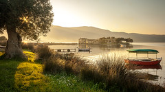 Misty Sunset & Old Mansion (Nick Panagou) Tags: light sunset sea sky plants seascape mountains building tree nature water grass contrast docks landscape boats gold spring colours outdoor spirit artificial greece sunsetlight goldenhour olivetree dockyard waterscape sunstar artificialnature greatphotographers thessaly flickrsbest bestshotoftheday magnesia canon400d flickrbest bestphotographer canonefs1855mmf3556isii