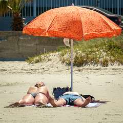 One Up, One Down (Steve Crane) Tags: woman man beach strand umbrella southafrica bikini boardshorts swimsuit swimwear westerncape helderberg