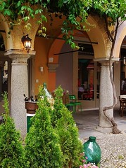 a quiet corner (SM Tham) Tags: light italy plants building lamp square restaurant town chairs bottles arcade columns vine arches cobblestones corks lakeorta italianlakes ortasangiulio piazzamotta