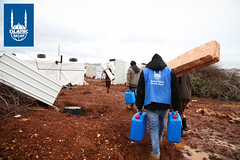 Islamic Relief workers giving out fuel cartons to people living in tents in Lebanon.