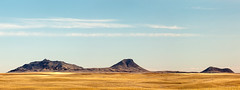Three Buttes (www.toddklassy.com) Tags: travel blue sky panorama brown west field grass horizontal clouds landscape buffalo montana long day mt escape unitedstates flat empty indian horizon nobody nopeople tribal panoramic hills erosion formation nativeamerican pasture journey american western land remote lonely concept prairie copyspace wilderness plains bison grassland surrounded emptiness spaces assiniboine reservation distant hays buttes wideopen greatplains geological destinations grosventre nakota extremeterrain blainecounty fortbelknap threebuttes fortbelknapindianreservation