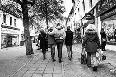 Couple walking with their arms around each other. (pootlepod) Tags: life street blue trees winter people blackandwhite white abstract black green classic love monochrome female naked walking photography perfect shoes shoot raw arms legs pavement january surface lovers sidewalk devon together shops pedestrians paving daisy backs bags stores pure period gender shoppers newtonabbot precinct purity strolling brassai arminarm canon60d baranches stphotographia
