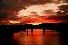 A Fiery Tennessee River Sunset (Roland 22) Tags: sunset red orange reflection beautiful yellow clouds golden haze flickr glow horizon gray angry rays walnutstreetbridge lightshadow flares humidity tennesseeriver marketstreetbridge veteransbridge chattanoogatennessee