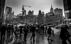 Rainy Bryant Park (davidjhumphries) Tags: park street city nyc blackandwhite newyork building rain skyline architecture umbrella canon moody traffic manhattan busy rainy 5d empirestate ultrawide bryantpark brolly 1740mml 5dmkii
