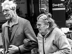 'Growing old is like being increasingly penalized for a crime you haven't committed.' ~ Pierre Teilhard de Chardin (pootlepod) Tags: life street old autumn winter people blackandwhite woman man male senior monochrome sex female hair walking photography glasses living twilight hands couple raw arms display pavement candid coat content sidewalk devon jacket elderly kindness mills spectacles citizen helping crook oap trago stmarychurch escorting stphotographia