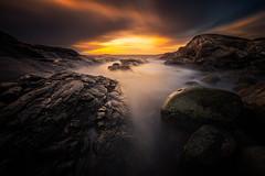 Ocean Darkness (Arvid Bjrkqvist) Tags: ocean longexposure sunset sky orange sun water colors fog clouds fire coast rocks soft stones smooth calm burning smoky milky tranquil fiery