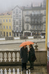 People with umbrella in town of Sintra, Portugal (jackie weisberg) Tags: plants green portugal wet umbrella village sintra eu palace unescoworldheritagesite rainy shrubs shrubbery resorttown orangeumbrella royalsanctuary jackieweisberg moorishandmanuelinestylesintranationalpalace