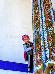 Little Bhutanese boy playing against white wall (Shutter Shooter) Tags: travel boy white playing tourism wall kid tour bhutan little sweet buddha buddhist fulllength young buddhism hideandseek thimpu isolated bhutanese lowangle thimphu mischiveous piller 2013
