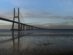 Vasco Gama bridge afternoon (biktoras07) Tags: bridge blue winter sunset sky moon white reflection building portugal water clouds river concrete outside afternoon mud outdoor lisbon victor santos rodrigues vasco tagus gama vascodagamabridge