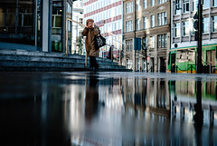 shrill (ewitsoe) Tags: street city winter urban woman sun reflection water lady 35mm walking puddle mirror nikon cityscape shadows sunny pedestrian reflected poznan watery poalnd d80 nikond80 ewitsoe erikwitsoe