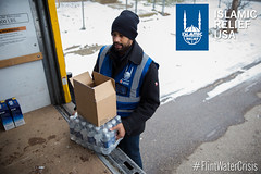Islamic Relief USA volunteers go to door to door handing out cases of water bottles and filters