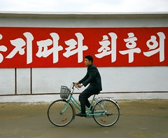 Along the banner (Frhtau) Tags: street people building girl del yard rural way asian design photo asia do leute outdoor path strasse text political main watching north banner picture scene korea du billboard east schild korean landschaft slogan pioneer fahrrad nord norte weg bycicle core corea dprk juche coria hinweisschild coreia nordkorea roade    strasenschild