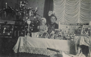Little girl with her doll and doll house on Christmas