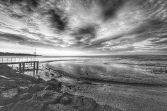 Cold early morning West Kirby beach (cathbooton) Tags: morning sea sky blackandwhite cold reflection beach clouds canon sand rocks jetty curves wideangle hills hdr wirral westkirby merseyside