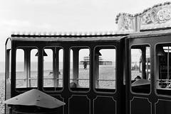 Through the window of a train...Brighton. (Sean Hartwell Photography) Tags: sea england blackandwhite holiday english film beach monochrome 35mm sussex pier seaside brighton shingle ground fair westpier ilfordhp5 rides merrygoround southcoast funfair amusements channel