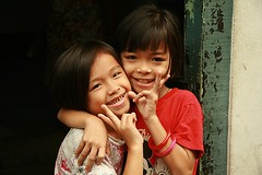 cute girls sending you peace from their doorway (the foreign photographer - ) Tags: girls two signs portraits canon children thailand kiss pretty peace bangkok khlong bangkhen thanon 400d
