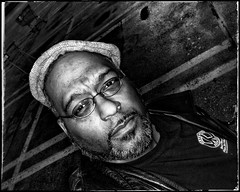2016.01.08  Day 008 (HTRM2) Tags: blackandwhite bw selfportrait man black male apple rain leather self beard glasses slick parking lot tshirt monochromatic jacket cap africanamerican aged grayscale middle asphalt ios spectacles app askew 40s greyscale newsboy iphone 2016 htrmiller2 snapseed iphone5s