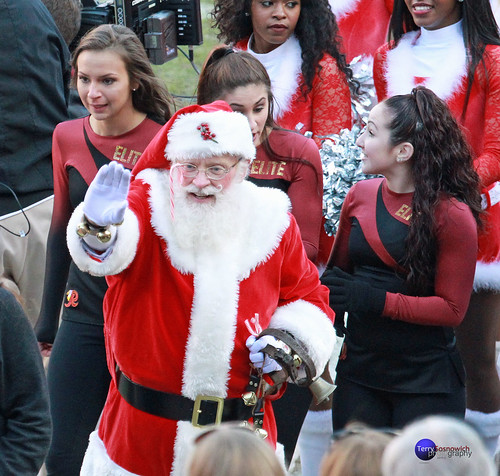 Santa waves to the fans with dancers and cheerleaders behind him.