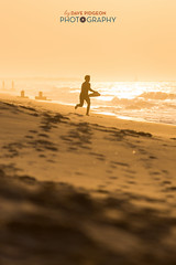 Skimboarding in Cape May (davepidgeonphotography) Tags: ocean beach silhouette yellow sunrise dawn newjersey sand may capemay atlanticocean wetsuit skimboard skimming 2015