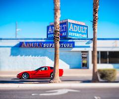 Toy Vegas: Superstore (miemo) Tags: street travel red sky usa blur car facade store spring downtown lasvegas bokeh nevada olympus palm palmtree storefront thestrip minimalism asphalt sportscar omd tiltshift adultstore faketiltshift olympus1240mmf28 em5mkii