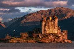 Sunset at Castle Eilean Donan (cheese and pickle) Tags: uk blue sunset mountain mountains color colour castle water beautiful beauty landscape scotland stream shadows britain outdoor flag scottish loch atmospheric scottishhighlands heritate