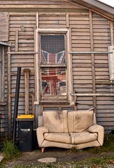 Couch (stephen trinder) Tags: wood old uk newzealand christchurch england building texture window shop outside exterior decay flag seat bin used couch sofa nz rubbish kiwi unionjack weatherboard settee draped christchurchnewzealand stephentrinder stephentrinderphotography