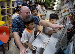 Sailor shows photographs of USS Chung-Hoon to children at Child@Street 11. (Official U.S. Navy Imagery) Tags: singapore navy underway deployment ddg93 usschunghoon greatgreenfleet