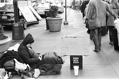 Sign of the Times (stillsguy) Tags: street nyc winter girls bw holiday up canon season hope 50mm homeless streetphotography pregnant tourists xp2 giving a1 cabs madisonsquaregarden ilford survivor lining fd hopelessness f12l